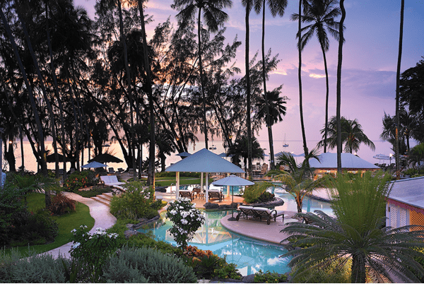 View of the swimming pool and bar at dusk in The Colony Club Barbados