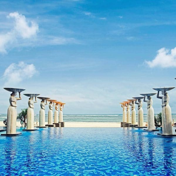 View across the swimming pool to the beach at Mulia Resort in Bali