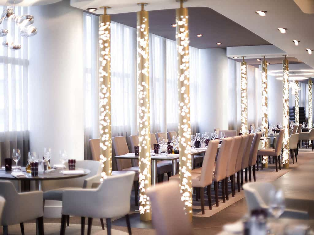 View of the restaurant at the Pullman Paris La Defense with lights on the pillars