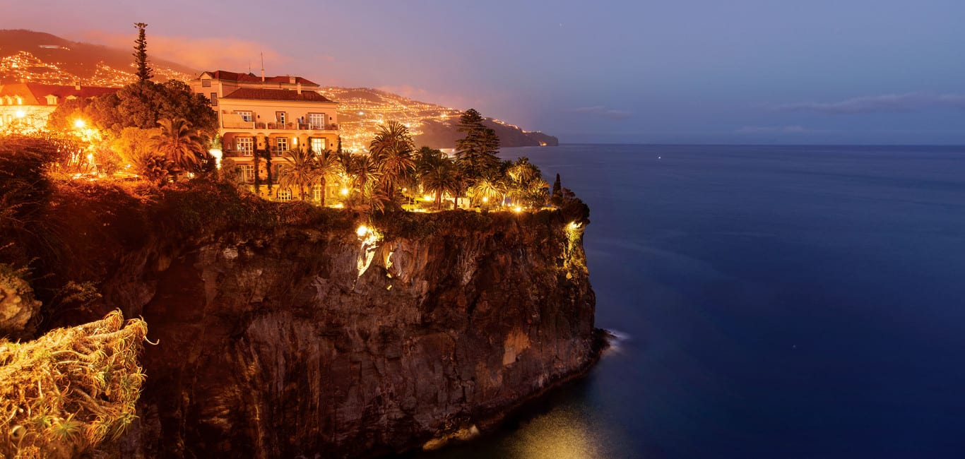 Night view overlooking the sea and the lights of the Belmond Reid's Palace in Funchal, Madeira
