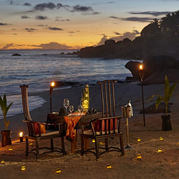 Romantic dining on the beach with candle light at Banyan Tree Seychelles