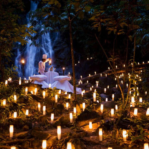 View of the romantic dining by the waterfall in the evening at The Sarojin, Khao Lak in Thailand