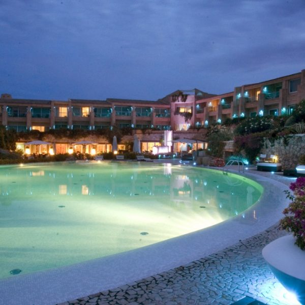 View of the swimming pool and resort in the evening at L Ea Bianca Luxury Resort in Sardinia