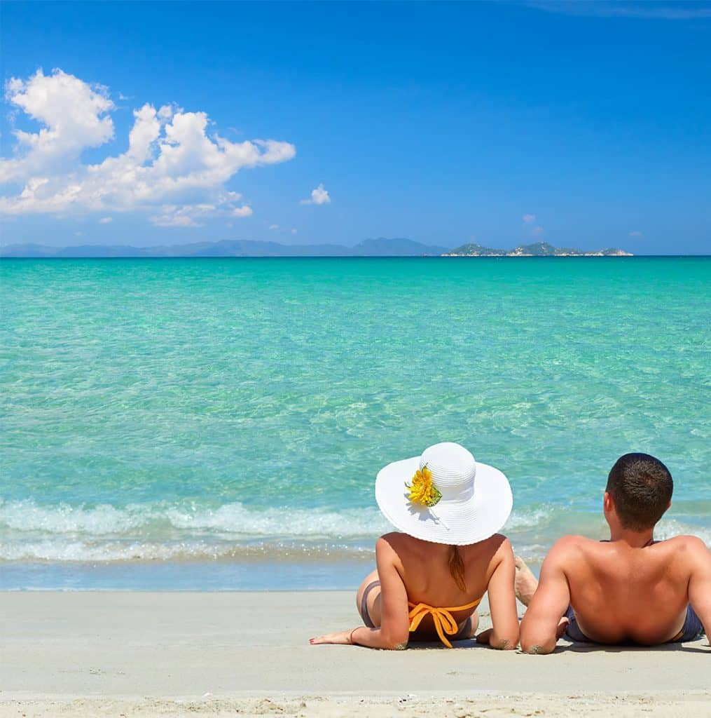 couple on beach enjoying holiday package arranged by luxury travel agents