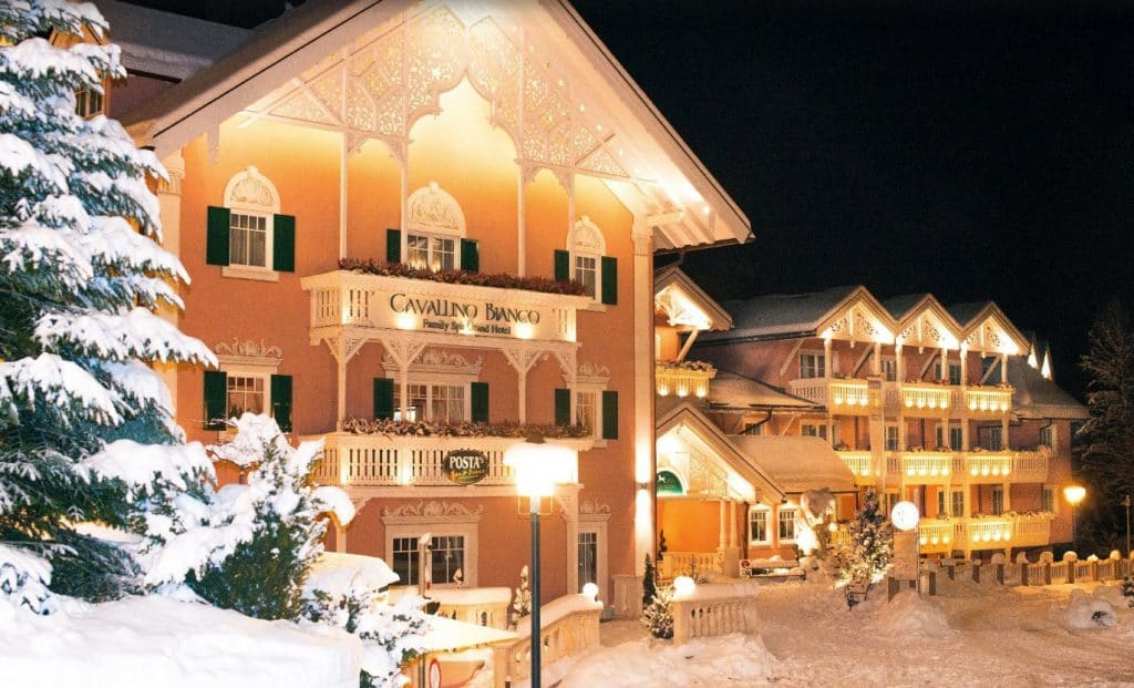 Cavallino Bianco luxury family friendly hotel italy snow covered building orange
