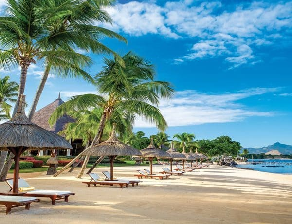 Beach view of The Oberoi Mauritius with sunbeds and parasols