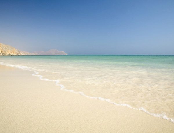 View of the sandy beach with the clear waves at Six Senses Zighy Bay in Oman