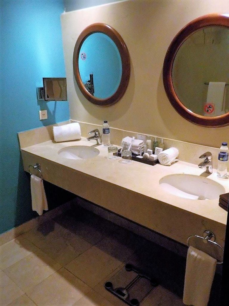 View of the his and hers sinks and vanity areas in the bathroom of the Preferred Club Partial Ocean View room at Now Larimar Punta Cana