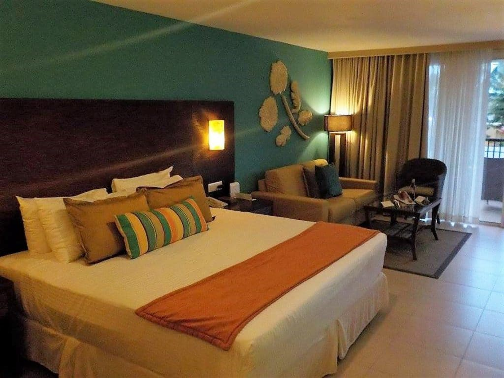View of the king size bed and the lounge area in the Preferred Club Partial Ocean View room at Now Larimar Punta Cana