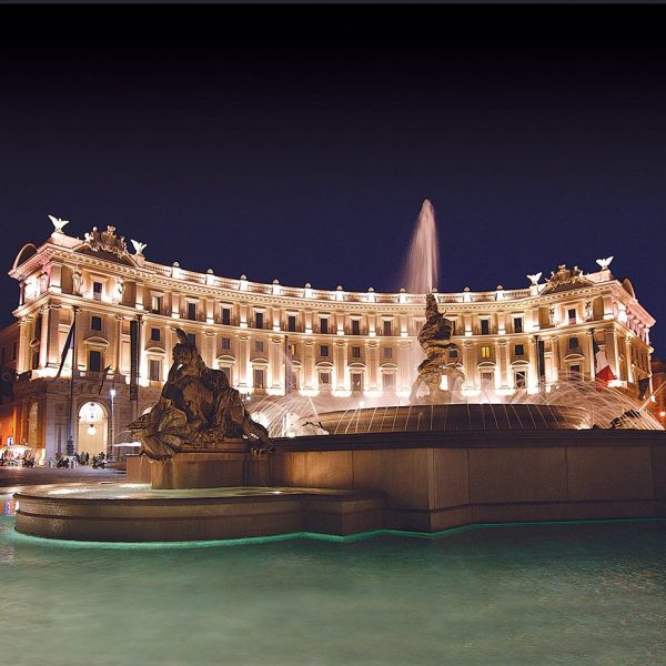 View of the exterior and fountain at night of the Boscolo Exedra Roma in Italy