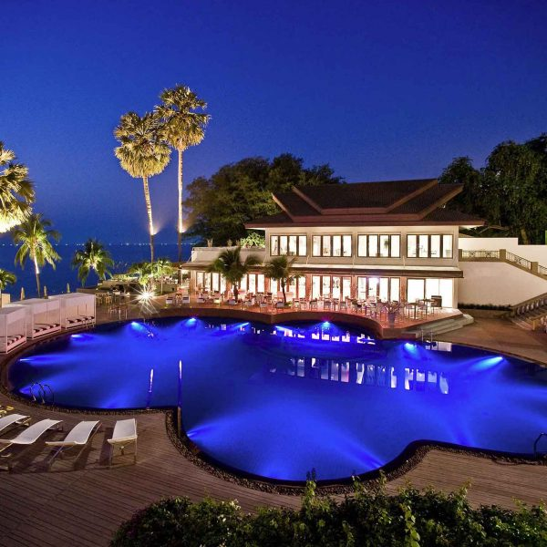 View of the swimming pool at night at the Pullman Pattaya Hotel G in Thailand