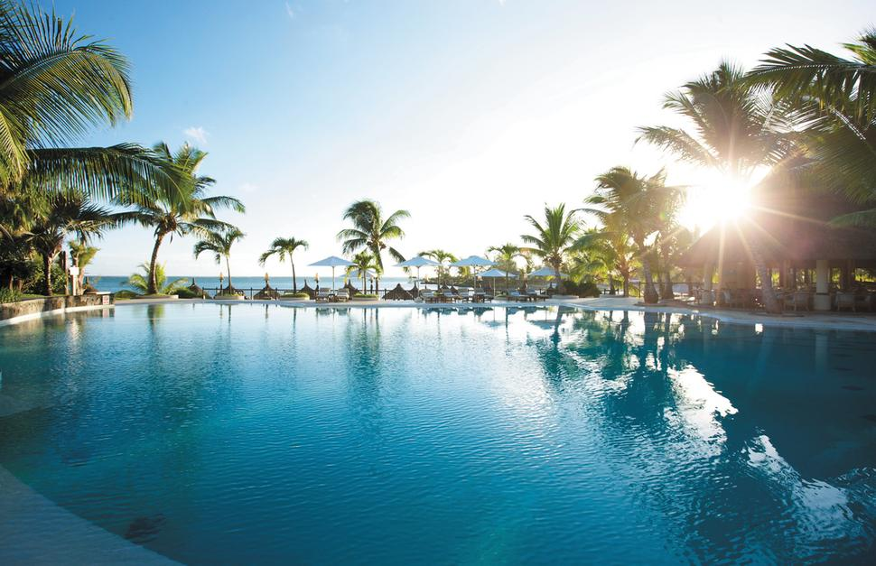 View of the swimming pool with the sun setting amongst the palm trees at LUX Grand Gaube in Mauritius