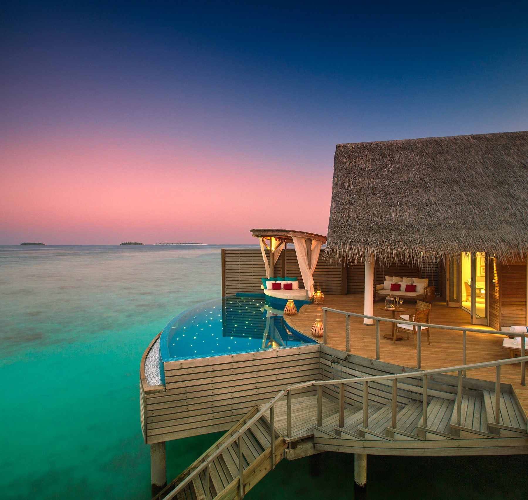 View across the Indian Ocean and the Water Pool Villa at Milaidhoo Island in the Maldives at dusk