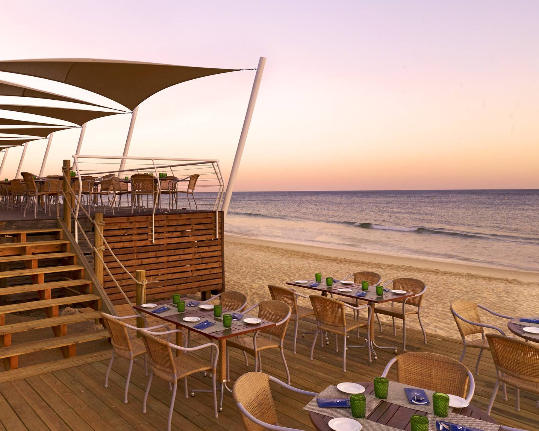 View of the beach and dining at dusk at Pine Cliffs, A Luxury Collection Resort in Algarve in Portugal