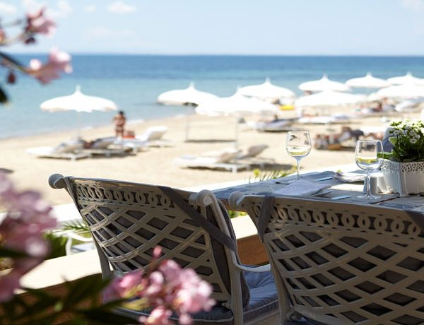 View of a dining table with chairs looking our towards the beach at Danai Beach Resort and Villas in Halkidiki