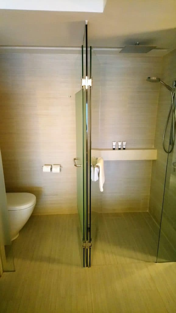 View of the toilet and the rain shower in the bathroom of a Panoramic Room at the Pan Pacific Singapore