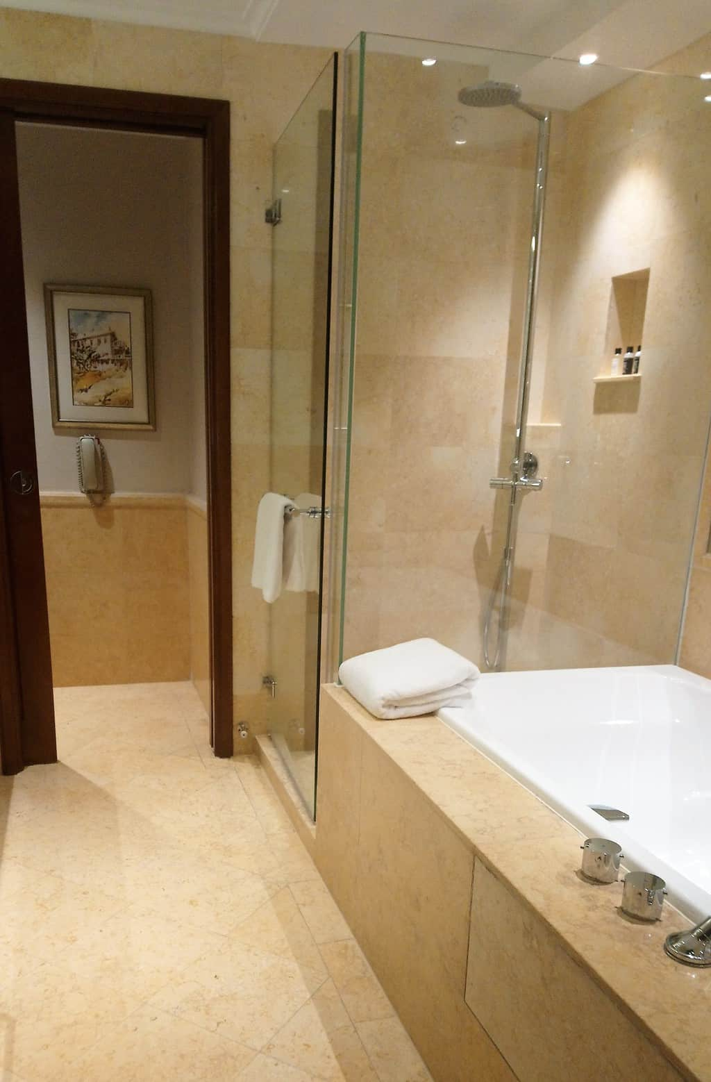 View of the bath and shower in the bathroom of a Premier Courtyard Room at The Fullerton Hotel in Singapore