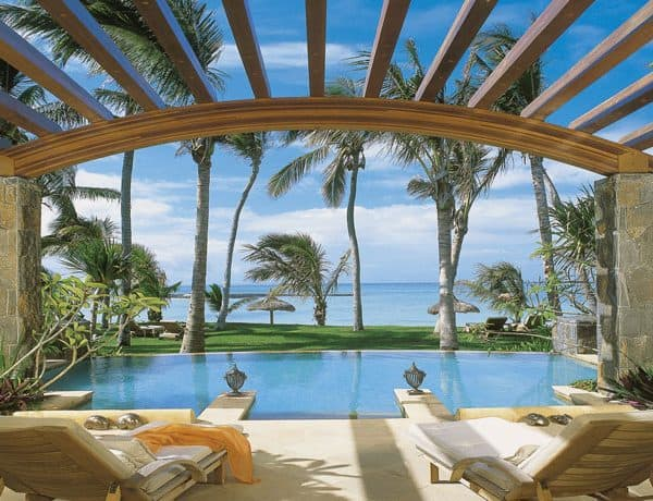 View of a private pool with two sun loungers and the Indian Ocean at One&Only Le Saint Geran in Mauritius