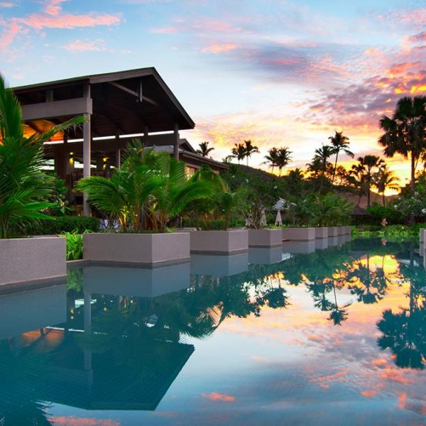 The Olympic-sized swimming pool at Kempinski Seychelles Resort at dusk