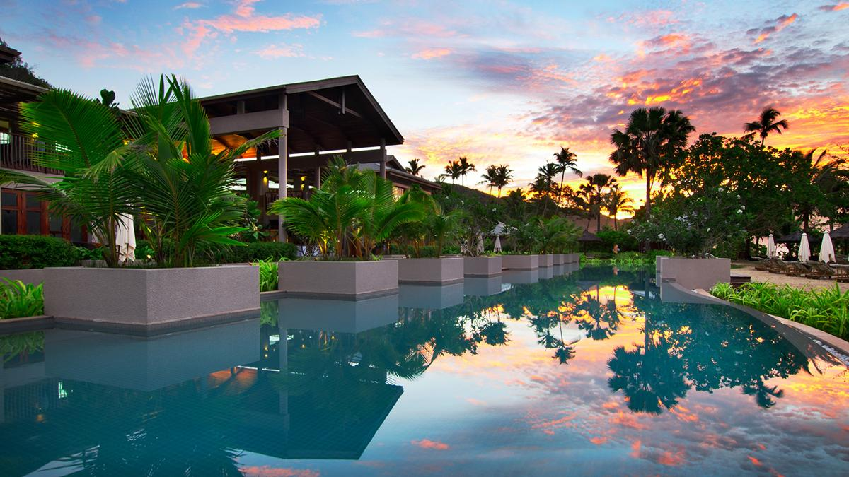 The Olympic-sized swimming pool at Kempinski Seychelles Resort at dusk